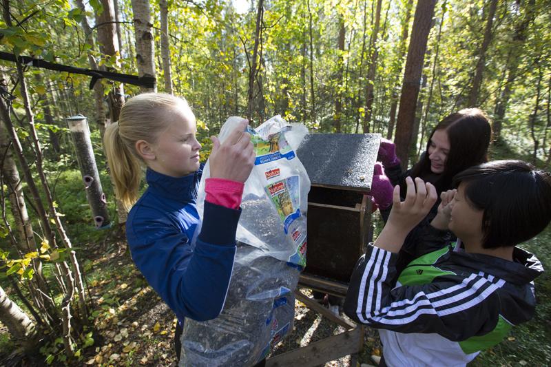 Emma Larsson, Camilla Karlström och Ellen Uusitalo fyller på mat åt fåglarna i Talvatisskogen.
